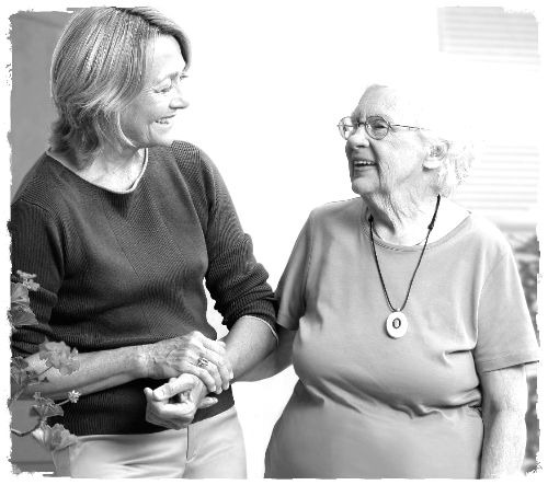 An elder wearing a medical necklace and talking to her daughter